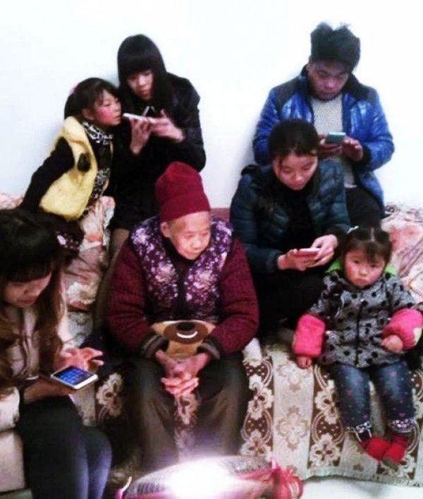 Hình ảnh sum họp gia đình thời công nghệ, bà già và đứa bé thể hiện sự cô đơn, lạc lõng trong khi các thành viên khác cắm mặt vào smartphone. (Ảnh: Internet)