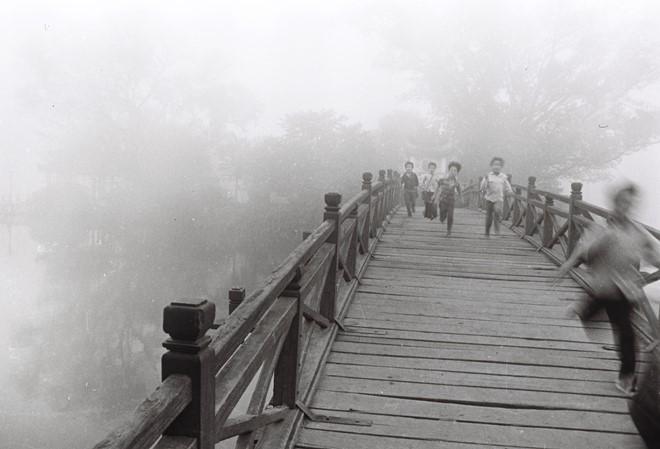 Những đứa trẻ nô đùa trên cầu Thê Húc dẫn vào đền Ngọc Sơn. Khi đó, cây cầu này màu đỏ son, làm bằng gỗ và có nhiều trụ liên tiếp.