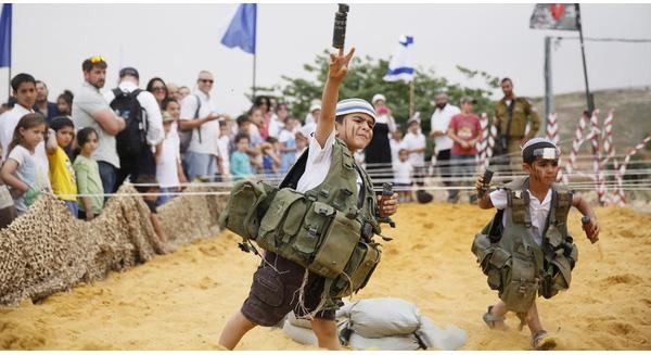 2 bé trai Israel mặc áo khoác quân nhân ném một quả lựu đạn giả trong buổi trưng bày vũ khí quân sự truyền thống đánh dấu kỷ niệm lần thứ 66 ngày độc lập của Israel vào năm 2014. Ảnh: Gali Tibbongali/AFP