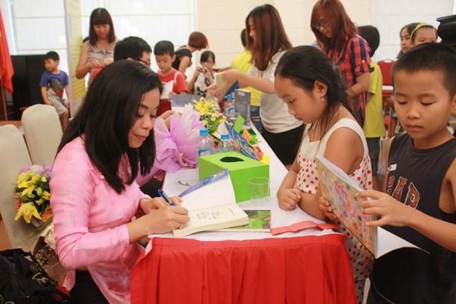 Nguyễn Phan Quế Mai tặng chữ ký cho độc giả nhỏ. Ảnh: Việt Hà
